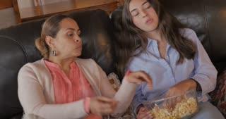 Adult latino woman and teen girl eating popcorn, talking and watching TV - handheld dutch angle shot
