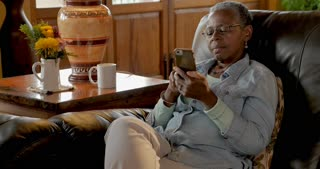 African American elderly senior woman in her 50s or 60s relaxing with her mobile phone reading and swiping while sitting on her living room couch during the day