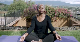 African American elderly woman in her 60s sitting quietly mediating with her legs crossed on a yoga mat outside - medium dolly shot