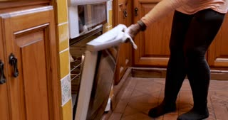 African American mature woman opens oven, removes fresh loaf of bread, and smells it then puts on stove top to cool in her home