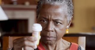 African American senior woman in 60s putting on glasses to read her prescription bottle