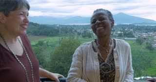 African American woman rubbing her face telling a story with her friends over 60 outside on a porch overlooking a mountain view