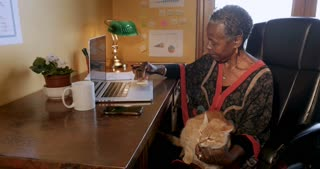 African American woman trying to work with an orange cat in her lap writing sticky note reminders