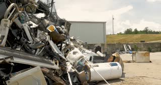ALEXANDER, NC, UNITED STATES - CIRCA MAY 2017 - Man throwing scrap metal into a large pile of recycled household trash and appliances at a recycling center, junkyard, transfer station, or landfill