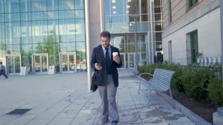 Ambitious executive millennial businessman with beard, briefcase, and to go coffee cup walking away from modern glass building and browsing on smartphone technology app in slow motion stabilized shot