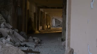 An abandoned hallway with crumbling bricks and debris in a hotel damaged during a major earthquake with erie sunlight shining in - dolly shot