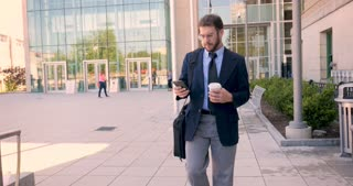 An ambitious frustrated executive millennial businessman with beard, briefcase, and to go coffee cup walking away from modern glass building and browsing on smart phone technology app stabilized shot