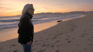 An attractive active mature woman talking and walking on beach at sunset in slow motion