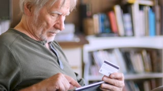 An attractive aging senior man ordering online with his credit card on his digital tablet at home