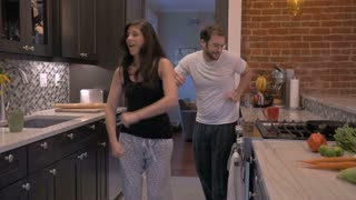 An attractive couple in early 30s dancing and celebrating in their pajamas in their home kitchen in slow motion