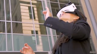 An attractive young businesswoman wearing VR goggles experiencing an augmented virtual reality 360 technology experience outside her office building in slow motion low angle