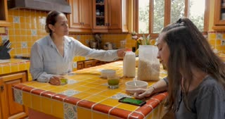 Annoyed Mexican mom yelling at her teenager daughter to stop using her cell phone with a green screen image and eat breakfast