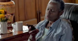 Annoyed senior black woman in her 50s or 60s answering her mobile phone and being bothered by the caller