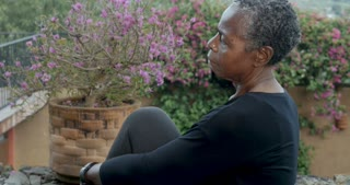 Attractive African American baby boomer in 60s woman moving into yoga half spinal twist pose