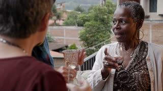 Attractive African American elderly woman in her 60s talking with her retired female friends outside on a terrace with wine and champagne in slow motion