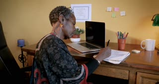 Attractive African American mature woman working and writing in a notebook at her desk in her office - dolly shot