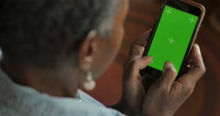 Attractive African American senior woman in her 50s or 60s texting with her thumbs on a green screen smart phone - OTS
