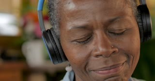 Attractive African American senior woman listening to music with her eyes closed wearing wireless headphones and dancing back and forth