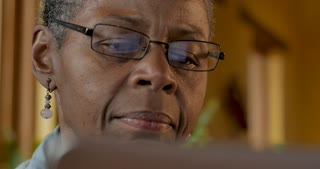 Attractive aging African American senior woman in her 50s or 60s reading her digital display such as a tablet or laptop screen