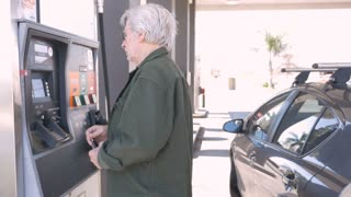 Attractive elderly man pumping gas into his car from a self serve gas station during the day