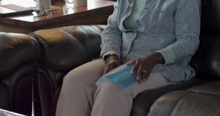 Attractive elderly senior black woman in her 50s or 60s feeling relief from icing her knee with an ice pack while sitting on her living room sofa during the day