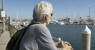 Attractive elderly senior in his 60s or 70s looking out at the water with boats docked in the marina - stabilized shot