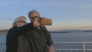 Attractive happy elderly couple in 60s take selfie with smartphone technology at sunset on ocean smiling and laughing together. Retired baby boomers using cell phone for photos and sharing on social media apps
