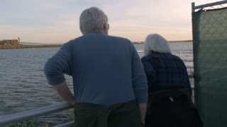 Attractive happy mature 60s couple looking at ocean and exploring. Retired man and woman enjoying their vacation traveling and exploring a bay along the water.
