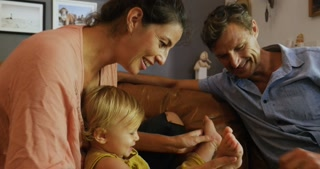 Attractive happy smiling family playing with their baby together with wooden toy blocks