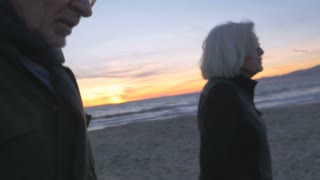 Attractive happy smiling mature 60s couple walking on beach at sunset. Retired fit elderly caucasian man and woman enjoying vacation exploring coast