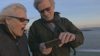 Attractive happy smiling mature couple in 60s using smartphone technology at sunset on ocean laughing together. Retired baby boomers using cell phone for photos and sharing on social media apps
