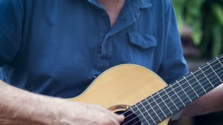 Attractive healthy aging senior man playing acoustic guitar outside in his garden tilt up