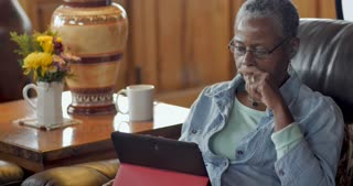 Attractive healthy, elderly senior black woman in her 50s or 60s using her digital tablet in her living room while sitting on the sofa