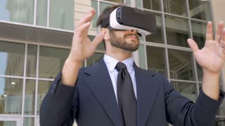 Attractive male business executive enjoying a 360 virtual reality experience with a VR headset outside his office building in slow motion low angle