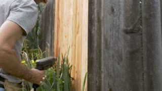 Attractive man in his 40s drilling a screw into a fence with an electric drill outside next to birds of paradise