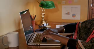 Attractive mature black woman having neck pain while working on her laptop in her home office
