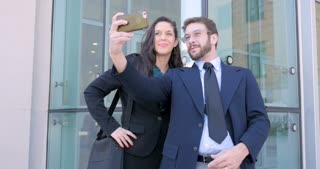 Attractive millennial business couple take selfie with cell phone technology app outside office building for social media or social networking in 4k