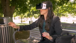 Attractive millennial female office worker in her 30s experiencing augmented 360 virtual reality with VR headset technology outside sitting on park hand held stabilized slow motion
