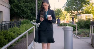 Attractive professional millennial businesswoman or lawyer on mobile phone technology walking on walkway with briefcase and to go coffee cup in 4k stabilized shot