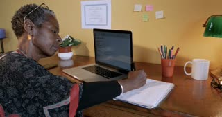 Attractive successful African American woman working at her desk writing in a notebook with a pen - dolly shot