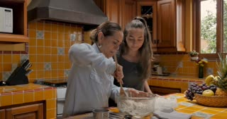 Attractive teenager daughter teaching her Mexican mom how to cook using an app on her cell phone - push in gimbal shot