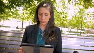 Attractive woman wearing business attire working on digital tablet mobile app technology on park bench stabilized hand held slow motion shot