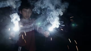 Attractive young 8 - 10 year old boy holding two burning sparklers and fireworks in his hands at night celebrating 4th of July Independence day holiday in slow motion