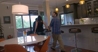 Attractive young couple in early 30s holding hands looking at a new modern home with their real estate agent