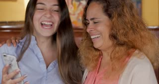 Authentic moment of a latino mom and teen daughter looking at cell phone and laughing both with the cell phone and without