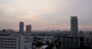BANGKOK, THAILAND - CIRCA NOVEMBER 2017 - Time lapse of the sunset against the skyline of skyscrapers near the trendy Ari neighborhood in Thailand with traffic moving from the cars below