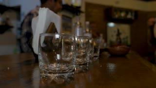 Bartender lining up empty shot glasses on a bar - close up