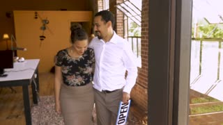 Beautiful and attractive happy smiling multi ethnic young couple holds an open sign for their small business in slow motion