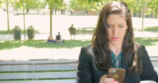 Beautiful happy woman in business fashion clothing sms texting or emailing on her mobile phone app technology on park bench dolly shot in 4k