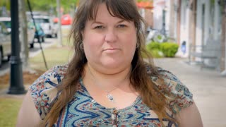 Beautiful plus sized model woman shaking her head no outside on urban city sidewalk during day